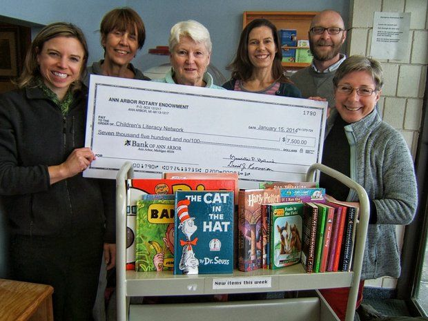 The Children'€™s Literacy Network team holding the large check they received from the Rotary Club of Ann Arbor. The $7,500 grant will support its Staying in Closer Touch program. (Courtesy of the Children's Literacy Network)